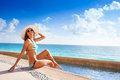 Happy woman in sunglasses with white hat sunbathes tanned under sun while sitting on stoned pier near to the ocean summer Stock Photos