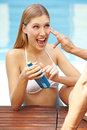 Happy woman with sunscreen bottle Stock Photography