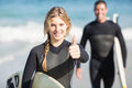 Happy woman with surfboard showing her thumb up women on the beach Stock Photos