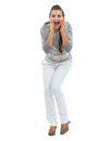 Happy woman in sweater shouting through megaphone shaped hands full length portrait of young Royalty Free Stock Photo