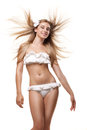 Happy woman in swimwear with blowing hair isolated slim tanned sexy white studio fabric Stock Photos
