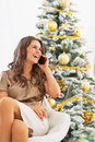 Happy woman talking cell phone while sitting near christmas tree portrait of young Royalty Free Stock Photo