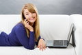 Happy woman talking on mobile phone and using laptop lying on sofa modern technology smiling typing computer keyboard surfing Stock Images