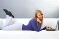 Happy woman talking on mobile phone and using laptop lying on sofa modern technology smiling typing computer keyboard surfing Stock Photos