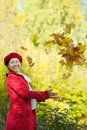 Happy woman throw up maple leaves mature Stock Image