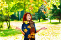 Happy woman is throwing autumn leaves Royalty Free Stock Photography