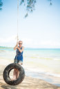 Happy woman on tire swing having fun at the beach phu quoc vietnam Royalty Free Stock Image