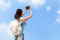 Happy woman traveler photo by tablet pc with blue sky Stock Photography