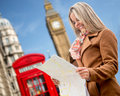 Happy woman traveling to london holding map Royalty Free Stock Image