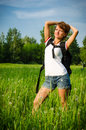 Happy woman turist in a summer field with backpack and bike Stock Images
