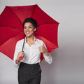 Happy woman with umbrella african american business standing red gesturing thumb up over gray background Stock Images