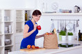Happy woman unpacking groceries kitchen home Stock Images