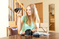 Happy woman unpacking new digital camera and objective at home a the table Royalty Free Stock Photos