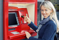 Happy woman using atm to withdraw money young Stock Images