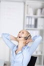 Happy woman using headset folding hands behind head Royalty Free Stock Photography