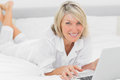Happy woman using her laptop on her bed smiling at camera in bedroom home Stock Image