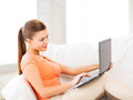 Happy woman using laptop at home picture of Stock Photo