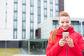 Happy woman using texting on smart phone outdoors on a city building background Royalty Free Stock Photo