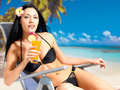 Happy woman on vacation on the beach brunette drinking orange juice Royalty Free Stock Photos
