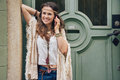 Happy woman wearing bohemian style clothes talking cell phone Royalty Free Stock Photo