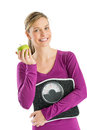 Happy woman with weight scale and smith apple portrait of young standing against white background Stock Photography
