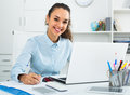 Happy woman working with paperwork and laptop Royalty Free Stock Photo