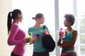 Happy women with bottles of water in gym Royalty Free Stock Photo