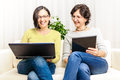 Happy women chat browsing home laptop Royalty Free Stock Photo