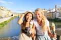 Happy women friends eating ice cream in florence on travel cheerful girlfriends enjoying italian food gelato cone smiling by Royalty Free Stock Images