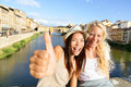 Happy women girl friends on travel in florence cheerful girlfriends thumbs up smiling portrait outdoor by ponte vecchio Stock Images