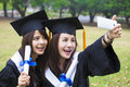 happy women in graduation gowns taking picture with cell pho Royalty Free Stock Photo