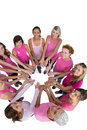 Happy women joined in a circle wearing pink for breast cancer on white background Royalty Free Stock Images