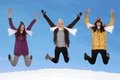 Happy women jumping in winter with gloves scarf and caps Stock Photos