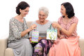 Happy women presenting mother with gifts bags Stock Images