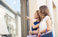 Happy women with shopping bags at shop window Royalty Free Stock Photo