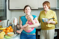 Happy women of three generations cooking fruit puree with blender in domestic kitchen at home Stock Photos
