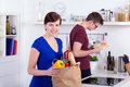 Happy women young men unpacking groceries kitchen Stock Photos