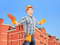 Happy worker holding a brick and spreading arms with a building manual in background Stock Photos
