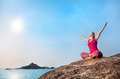 Happy yoga woman doing in red costume on the stone near the ocean in india Royalty Free Stock Image
