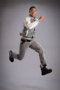 Happy young african american jumping in air male model on grey background Stock Images