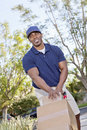 Happy young African American male pushing handtruck Royalty Free Stock Photo