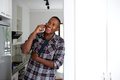 Happy young african guy at home making a phone call Royalty Free Stock Photo