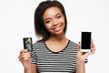 Happy young african lady using phone and holding debit card. Royalty Free Stock Photo
