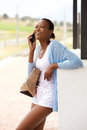 Happy young african woman with bag talking on mobile phone Royalty Free Stock Photo