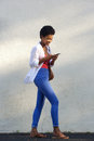 Happy young african woman walking on street using mobile phone Royalty Free Stock Photo