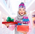 Happy young american woman with a christmas gift photo of in winter outerwear at shop Stock Image