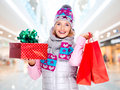 Happy young american woman with a christmas gift photo of in winter outerwear at shop Stock Photo