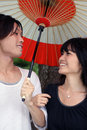 Happy young Asian couple smiling with umbrella Royalty Free Stock Images
