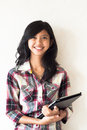 Happy young asian girl holding a tablet pc Stock Photography