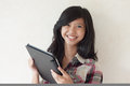 Happy young asian girl holding a tablet pc Royalty Free Stock Photos